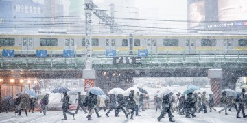 Snowy city with pedestrians and train.