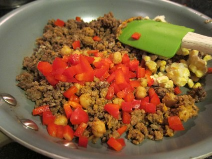 In a skillet put browned ground beef (or brown it!), leftover burrito filling use it up!), corn (frozen), red pepper diced. Using up lots of bits from previous meals.