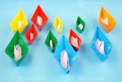 Stock photo colorful paper boats on blue surface