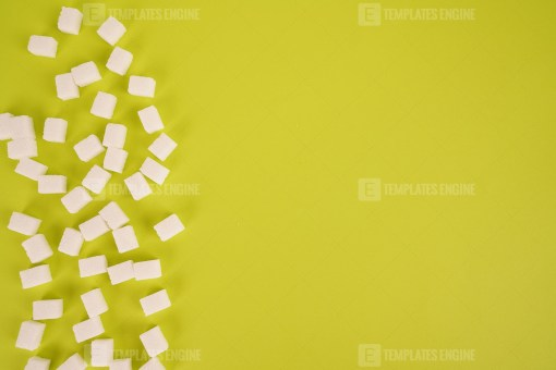 Lump sugar cubes on green background