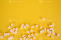 Lump sugar on yellow stock photo