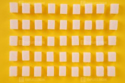 Pattern of white cubes of sugar on yellow background