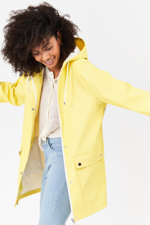 Lookbook d'une femme en manteau jaune et pantalon bleu sur fond gris