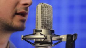 stock-footage-man-speaking-into-studio-microphone-mid-close-up-shot