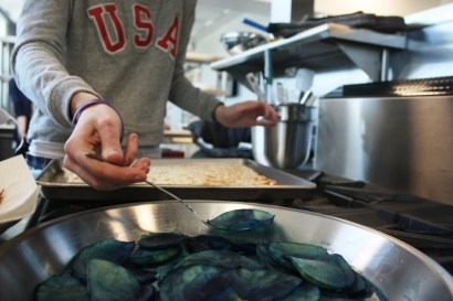 Adding our dyed potatoes as the blue of our American flag pizza.