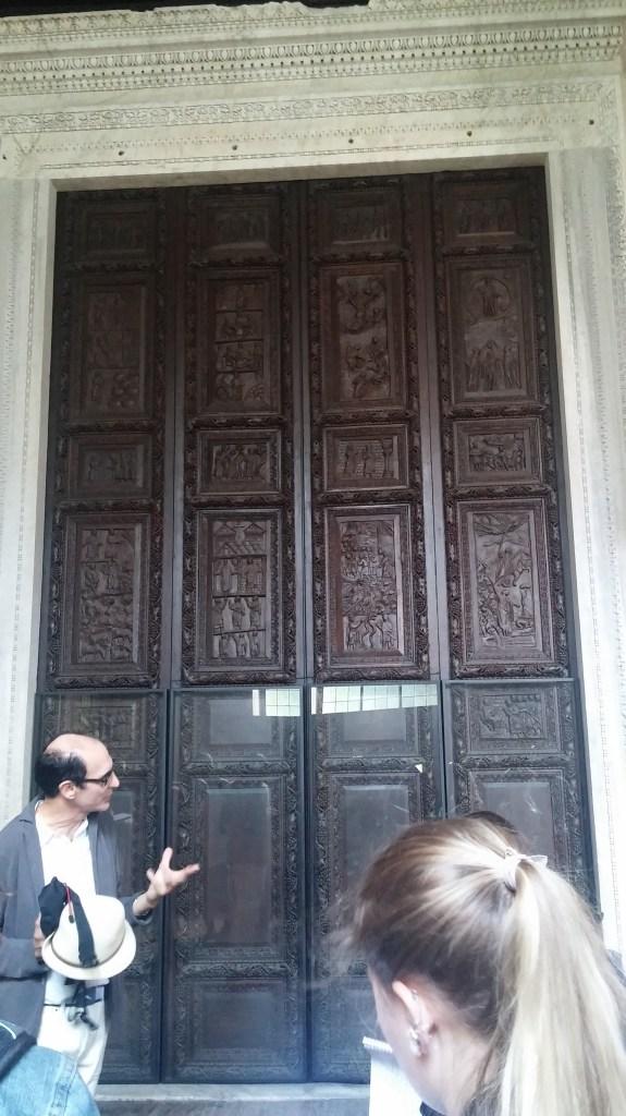 Prof, Carloni explaining that this door is still the original wooden door in santa Sabina, a church built in the fifth century