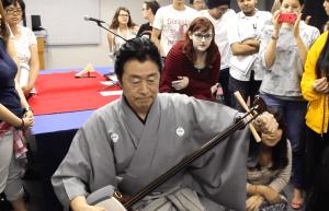 TUJ students eagerly watching Ichinosuke tuning his shamisen before teaching his first student.