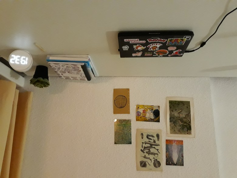 A large white desk featuring a laptop, books stacked upon each other, a plant, and a clock, The white wall perpendicular to the desk features six posters of different sizes.
