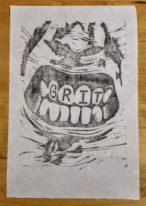 print of gritted teeth with the words GRIT written on the top teeth