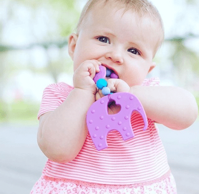 A baby biting on an elephant teething toy