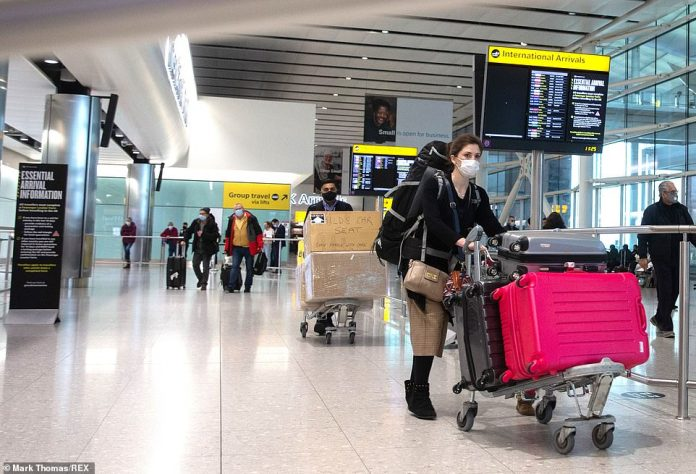 International passengers push their baggage through London Heathrow Airport after arriving at Terminal Two yesterday