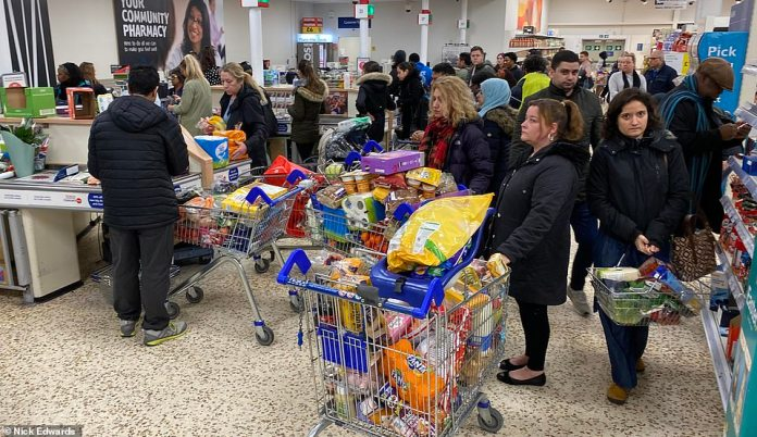 Shoppers stood in queues by the tills inTesco Extra in Surrey Quays, south east London on March 14, 2020