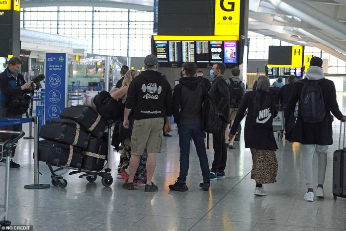 People seen queueing at check-in at Terminal 5 in Heathrow Airport today as global travel curbs ease