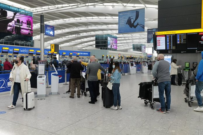 People queue up at check-in at the check-in desk at the departures area of London Heathrow Airport this morning