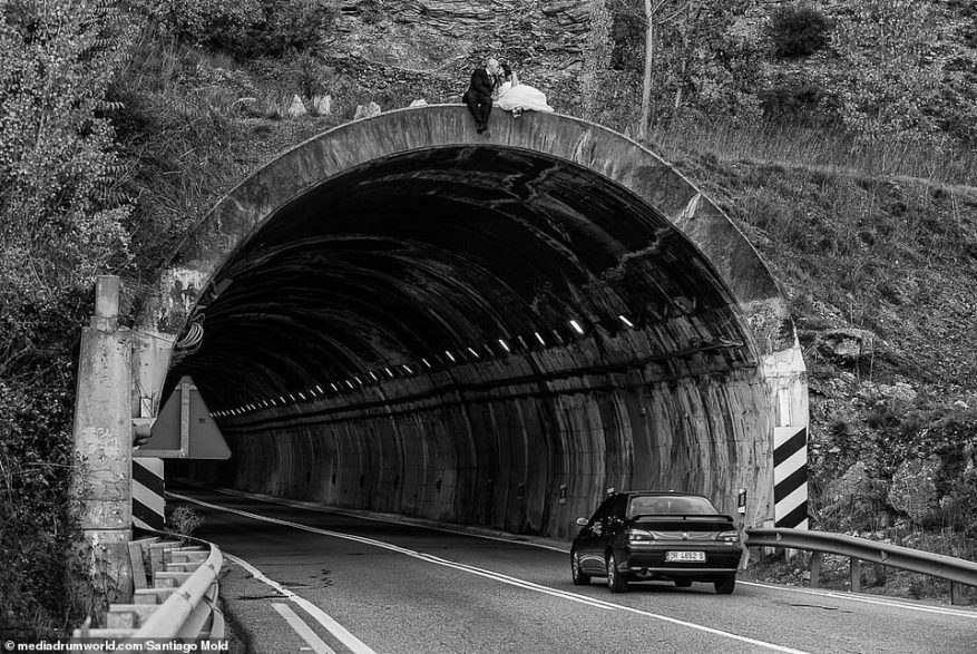 Need for speed:Santiago Moldes, from Ponferrada, Spain, captured a particularly unique photo of a bride and groom sharing a kiss while perched on the top of an underpass - as a seemingly-ignorant car drove beneath their dangling feet