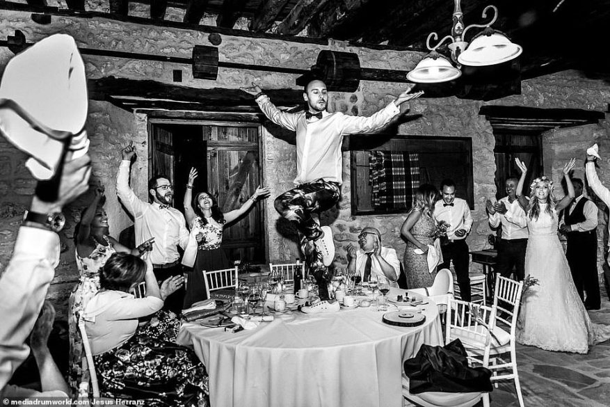 All singing, all dancing: Herranz is another photographer who landed two images in the list of award-winners, thanks to this celebratory snap, which shows a man in floral trousers dancing atop a table at a wedding, while his fellow guests crowd round to applaud his moves