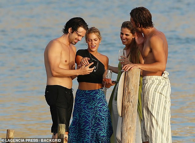 Good looking group: The genetically blessed group laughed and looked at snaps on the actor's phone