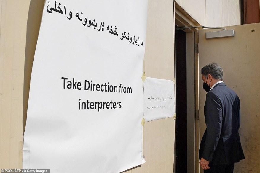 Afghan refugees and asylum-seekers are instructed to 'take direction from interpreters' as they arrive in Doah. Blinken is pictured entering a center where they will be housed before being sent to the U.S. for vetting