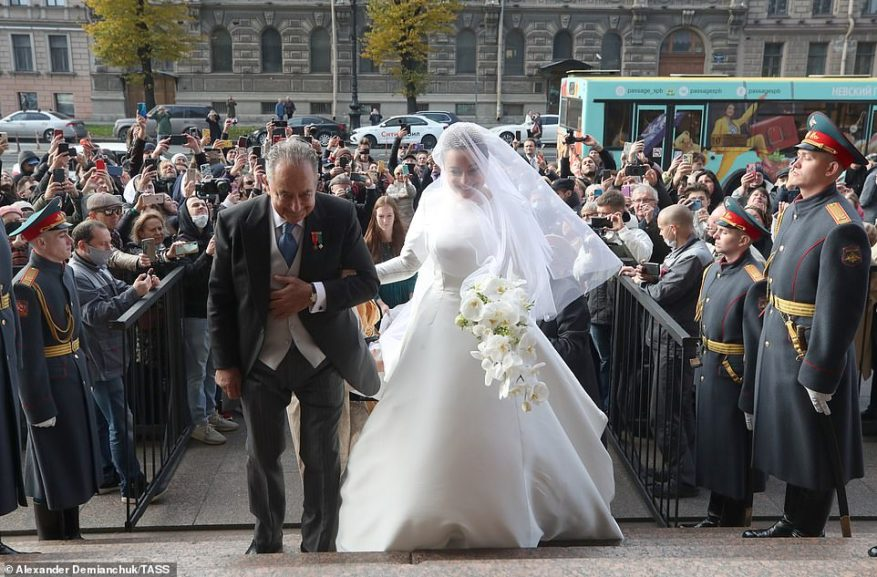 Crowds gathered outside the venue to wish the bride well as she arrived at the event with her fatherRoberto (pictured).