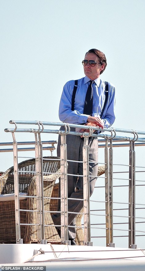 Look out: Another unknown actor was seen shooting scenes as he leant over the side of the boat