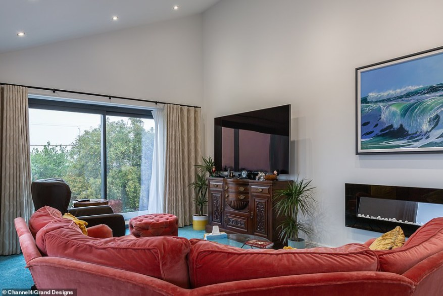 Geoff's finished living room (pictured) featured bold blue carpets, a red sofa and breathtaking views of the estuary