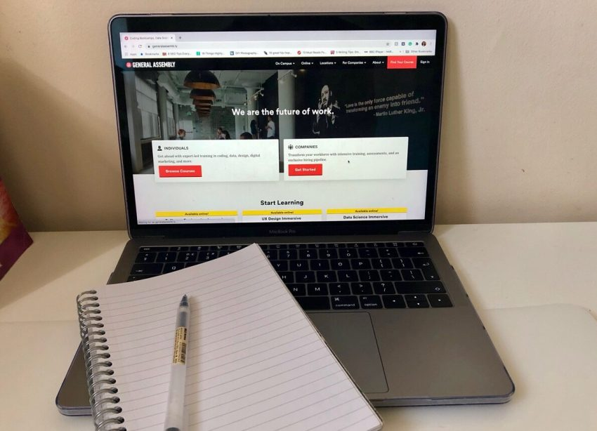 Photo of laptop and a blank notebook and pen