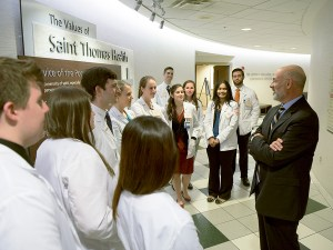UTHSC residents and Joe DiPietro at the entrance to the Linda & Mike Curb Institute for Advanced Medical Education