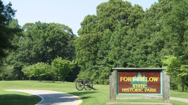 "Road with a Civil War cannon and sign reading ""Fort Pillow State Park"" off to the side. Trees in background"
