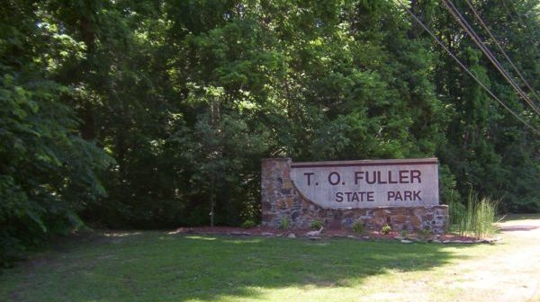 "Stone sign reading ""T. O. Fuller State Park"" at the edge of wooded area"
