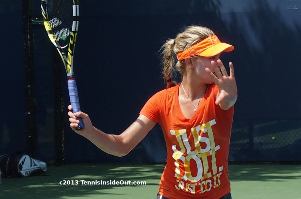 Eugenie Bouchard forehand swing palm forward talk to the hand Nike Just Do It T-shirt orange and yellow kit blonde ponytail braid Cincy 2013