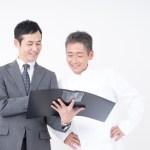 厨房機器購入を選定する男性2人