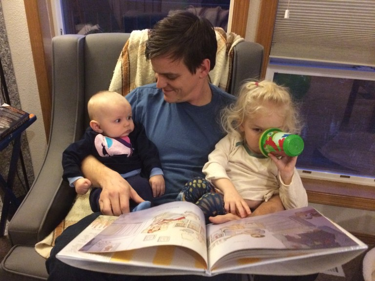 Dad sisters reading book