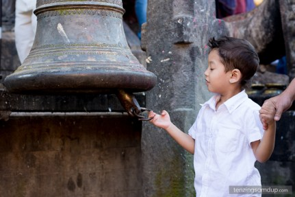 young boy ringing stone bell