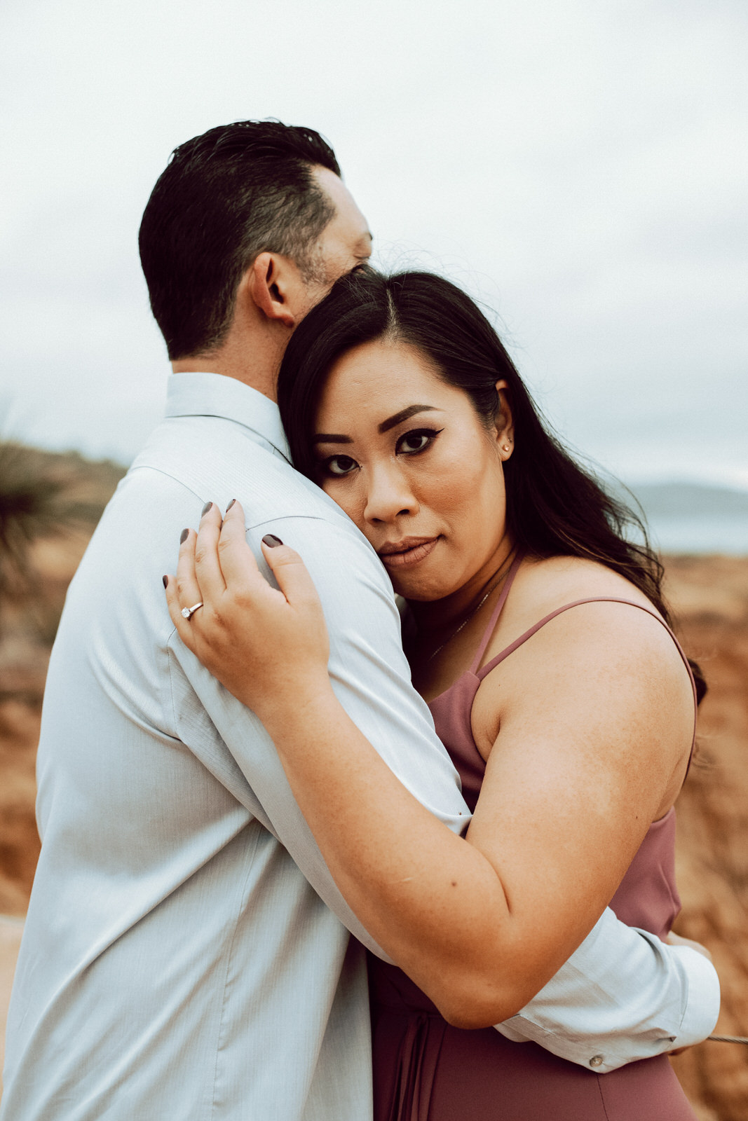 A man and woman embracing each other as she looks directly at the camera