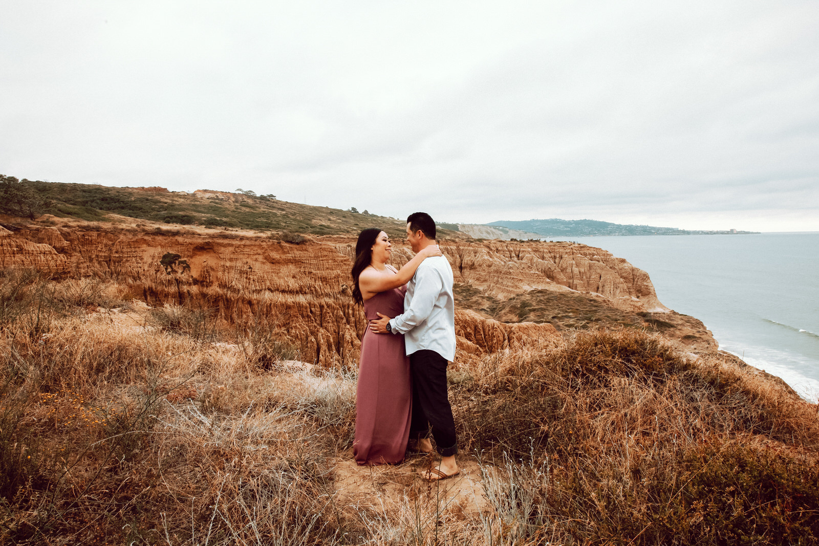 A man and a woman standing on a cliff with brown vegetation all around them holding on to each other and smiling