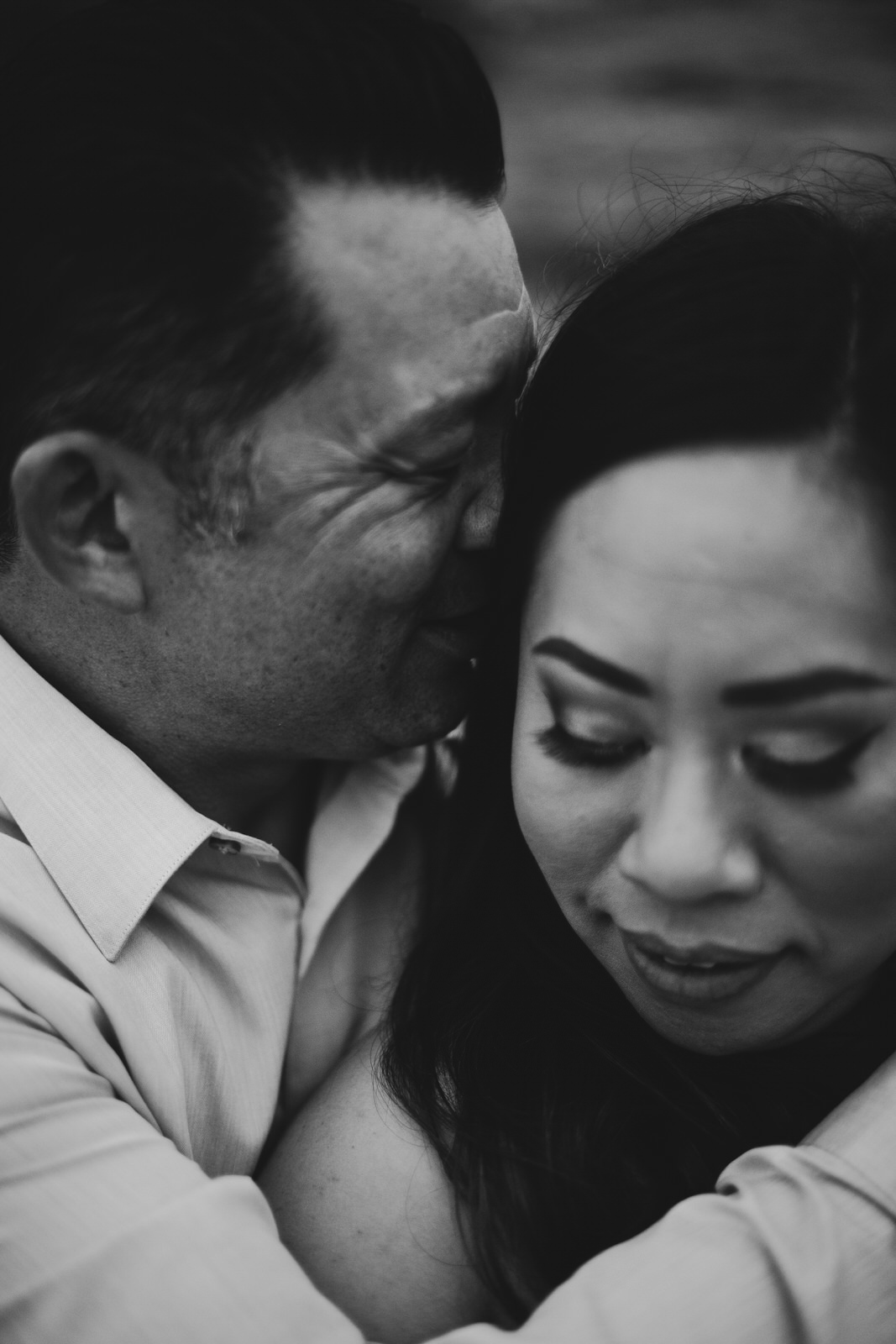 A black and white images of a man kissing a womans temple