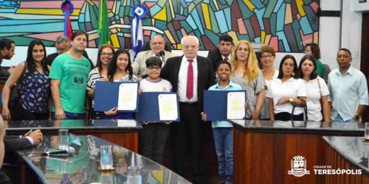 Os três alunos da rede municipal homenageados, com professores e familiares
