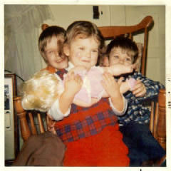 photo of Terry Grahl with her brothers and a baby doll