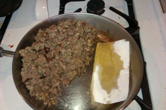 photo of crumbled, cooked sausage and a grease-soaked paper towel in a pan