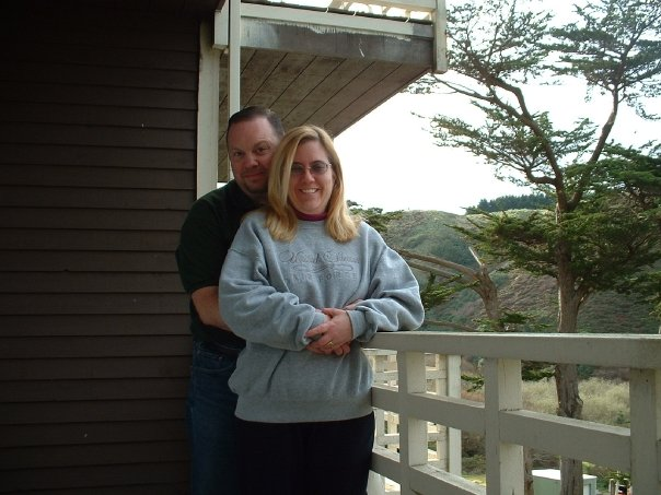 photo of the author and her husband with their arms around each other, posing on a balcony