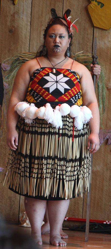 a Maori woman, in traditional clothing. Her lip and chin are tattooed