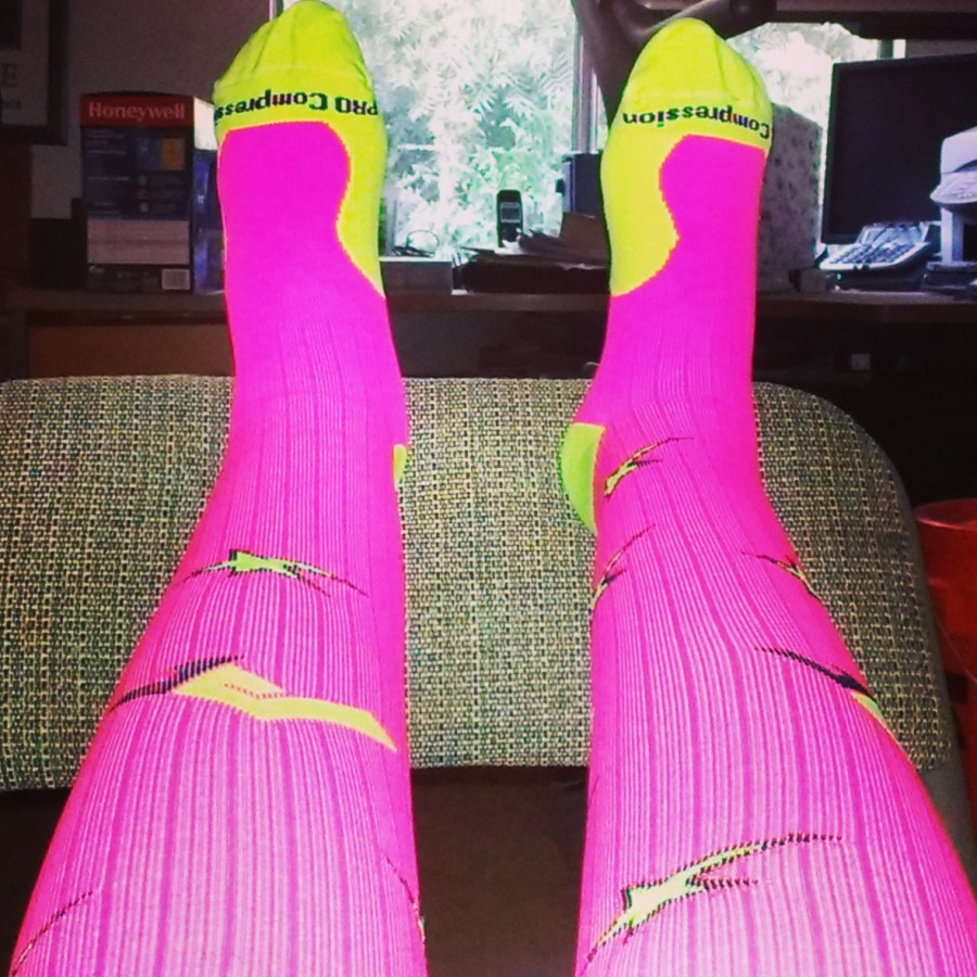 the author's feet in pink and yellow Pro Compression Marathon Socks