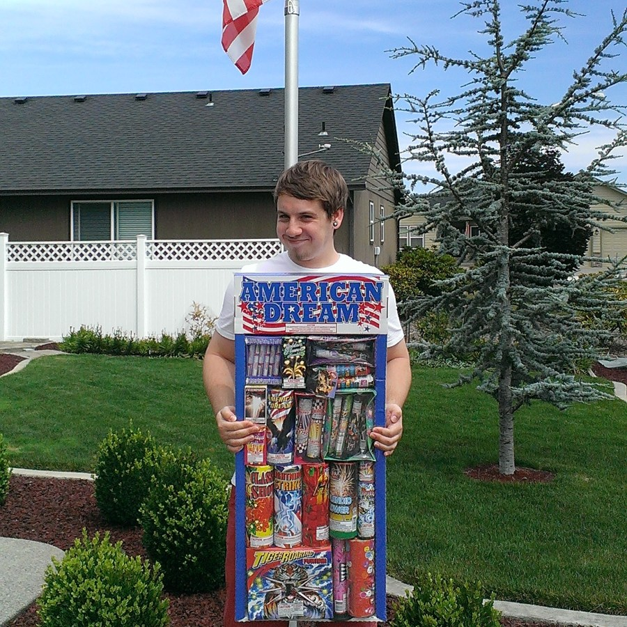 the author's son holding a giant box of fireworks