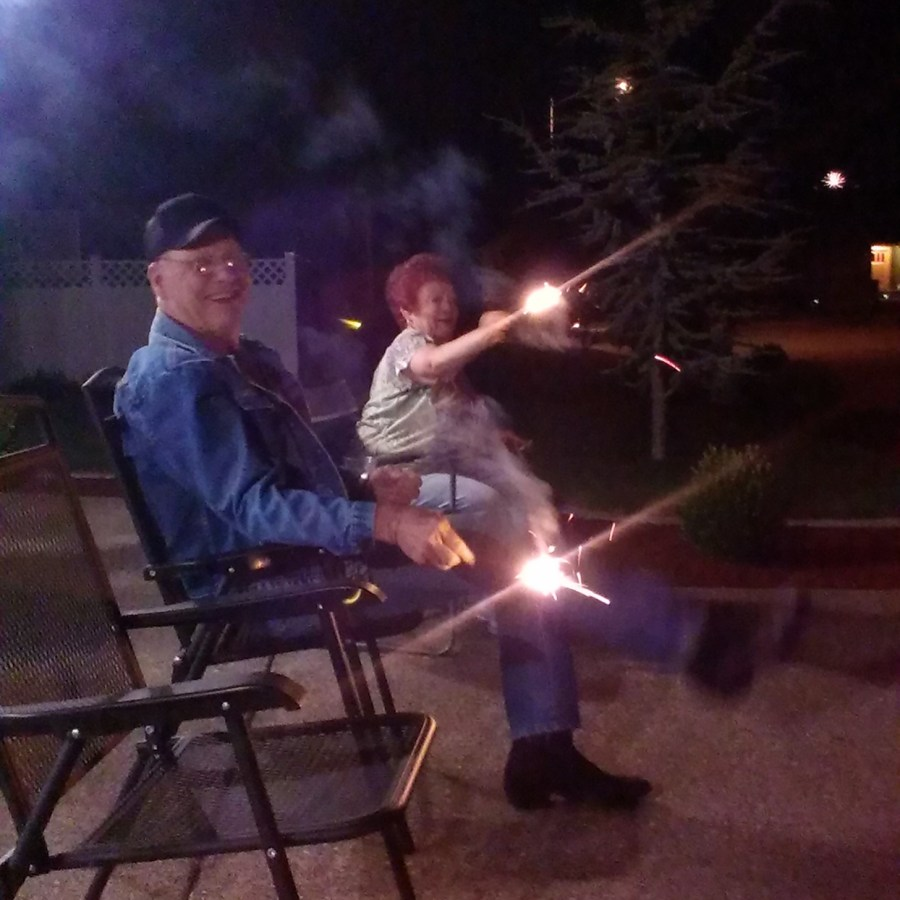 the author's in-laws smiling and holding sparklers