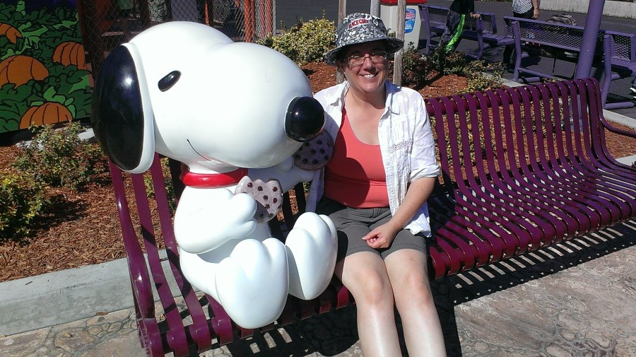 the author posing with a Snoopy statue