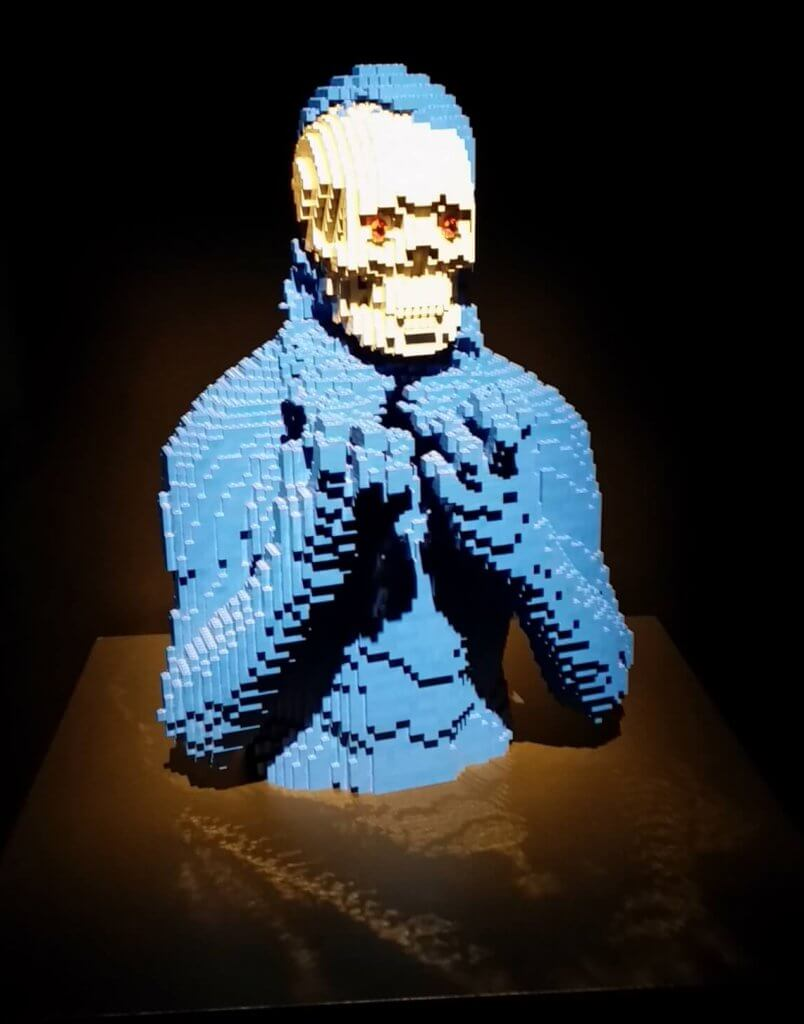 a Lego man peeling off the outer layer to reveal a Lego skull underneath