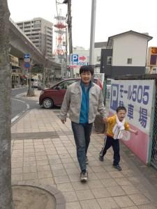 てらすやモール505専用駐車場の前に店主ハルと息子が手を繋いで歩いている