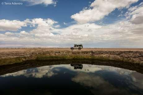Mochileiro sendo refletido nos Ojos del Salar, Atacama