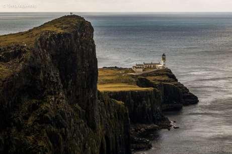 Duas pessoas observam o farol do alto do cliff