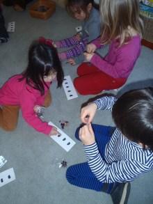 Nika, Ayleen, and Ken counting beans.